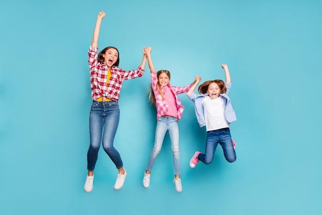 In voller länge körpergröße foto von zwei freudigen töchtern mit mutter gewinnen freudig weiß tragen jeans jeans, während mit blauem hintergrund isoliert