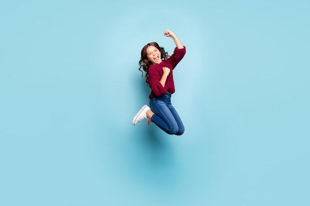 In voller länge körpergröße fröhlich positiv preteen springen freut sich isoliert blaue farbe wand