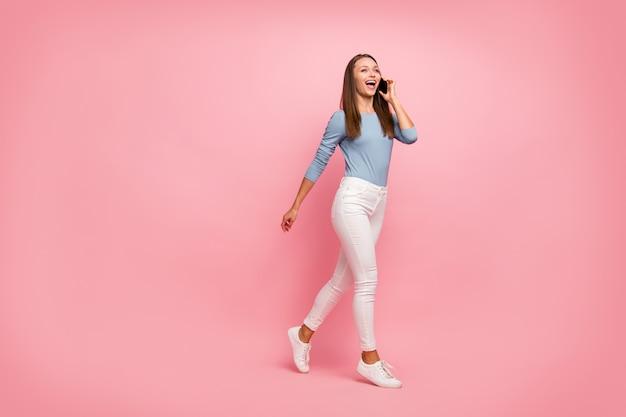 In voller länge körpergröße gedreht foto von fröhlichen positiven niedlichen netten hübschen mädchen in weißen turnschuhen blauen pullover lachen über witz von freund gehen isoliert pastellfarbe hintergrund