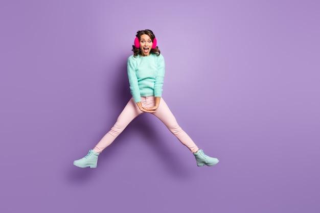 In voller länge porträt der hübschen dame hochspringen aufgeregt gute laune gespreizte beine seiten haben spaß tragen fuzzy pullover rosa ohrenschützer pastell hosen schuhe.