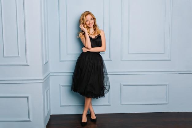 In voller länge porträt der schönen jungen frau mit welligem blondem haar, model posiert in stilvollen schwarzen spitzenkleid und schwarzen schuhen.