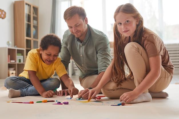 In voller länge porträt des jungen männlichen lehrers, der mit lächelnden kindern arbeitet, während spaß in der vorschule oder im entwicklungszentrum hat