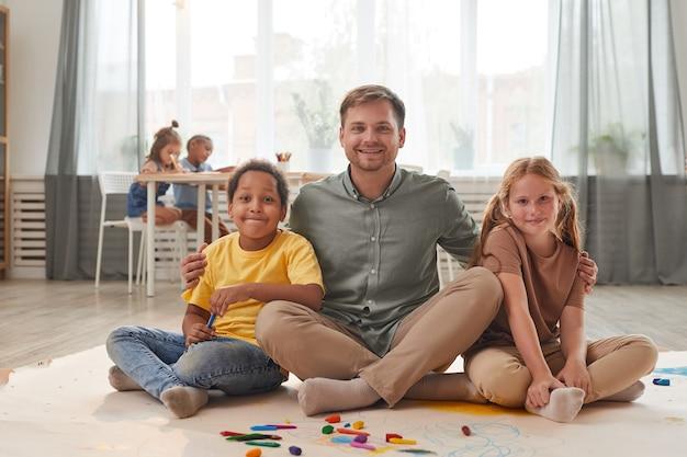 In voller länge porträt des jungen männlichen lehrers, der mit lächelnden kindern aufwirft, während spaß in der vorschule oder im entwicklungszentrum hat