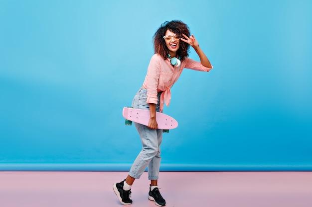 In voller länge porträt des lockigen mulattenmädchens in den schwarzen turnschuhen, die mit friedenszeichen nach dem eislaufen aufwerfen. innenfoto der aufgeregten afrikanischen dame mit skateboard, das vor der blauen wand mit lächeln steht.