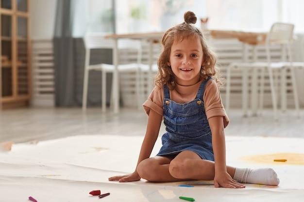 In voller länge porträt des niedlichen kleinen mädchens lächelnd sitzen auf dem boden im spielzimmer und zeichnen