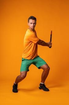 In voller länge porträt eines tennisspielers mann in aktion gegen orange hintergrund nahaufnahme