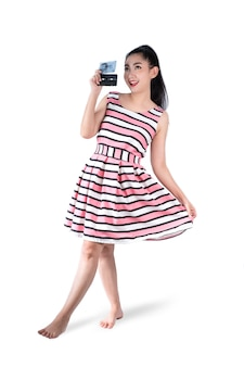 In voller länge porträt junge asiatische frau in retro mode rosa kleid hält eine kassette auf einem weißen hintergrund
