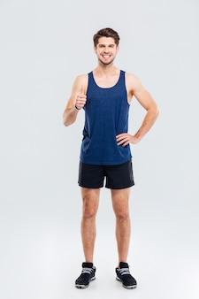 In voller länge portrait eines glücklichen fitness-mannes, der daumen nach oben isoliert auf grauem hintergrund zeigt