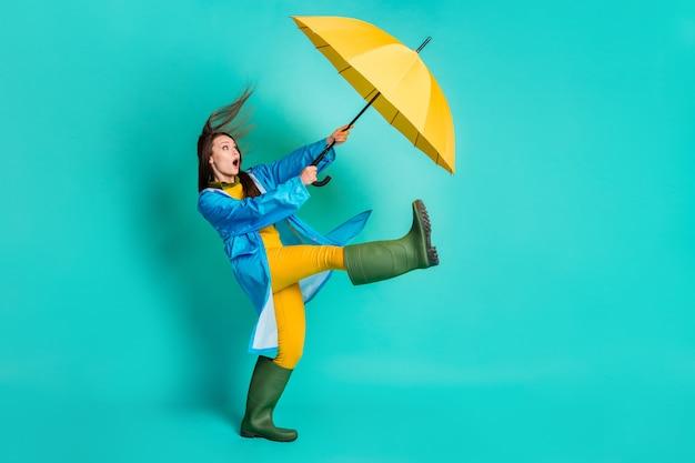 In voller länge profil schockierte dame stürmisches wetter spaziergang halten regenschirm