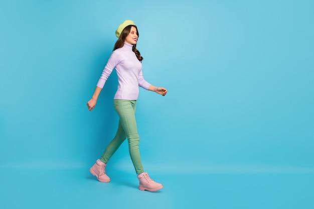 In voller länge profilfoto der hübschen touristin dame gehen straße ins ausland reisende tragen grüne baskenmütze hut lila rollkragenpullover hosen schuhe schuhe stiefel isoliert blaue farbe wand