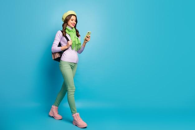 In voller länge profilfoto der hübschen touristin dame straße im ausland durchsuchen telefon tragen tasche grüne baskenmütze rollkragenpullover schal stiefel isoliert blaue farbe wand