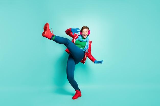 In voller länge profilfoto der lustigen dame heben bein hoch tanzen seltsame seltsame bewegungen tragen lässig roten mantel schal rosa ohrenschützer hosen pullover handschuhe schuhe isoliert blaugrün farbe wand