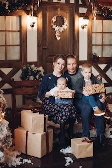 In voller länge stock porträt der jungen kaukasischen familie mit zwei kindern, die auf bank mit weihnachtsgeschenken kuscheln