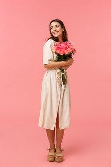 In voller länge vertikales porträt romantische ekstatische junge frau, die rührendes geschenk empfängt, niedliche blumenstraußrosen umarmend, träumerisch und entzückt schaut, nachdenklich lächelnd, rosa wand lächelnd