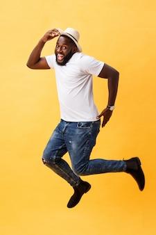 In voller länge vom hübschen jungen schwarzen mann, der gegen gelben hintergrund springt.