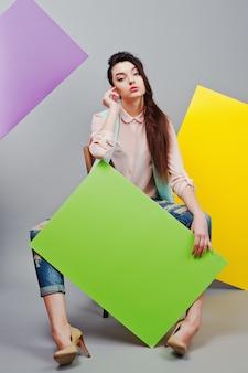 In voller länge vom schönen mädchensitzen, grüne leere werbetafel, über grauem hintergrund und gelber und violetter fahne halten