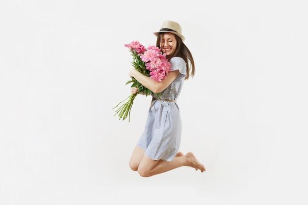 In voller länge von der glücklichen jungen frau des spaßes im blauen kleid, hut, der blumenstrauß der rosa pfingstrosen hält, springen lokalisiert auf weißem hintergrund. valentinstag, internationaler frauentag-feiertagskonzept.