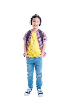 In voller länge von der jungen asiatischen jungenstellung und -lächeln über weißem hintergrund