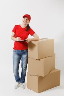 In voller länge von der lieferungsfrau in der roten kappe, t-shirt lokalisiert auf weißem hintergrund. weiblicher kurier, der klemmbrett mit papierdokument hält, leeres leeres blatt auf leeren kartons. paket empfangen.
