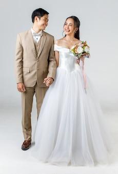 In voller länge von jungen attraktiven asiatischen paaren, mann mit beigefarbenem anzug, frau mit weißem hochzeitskleid, das zusammen händchen haltend steht. konzept für die fotografie vor der hochzeit.