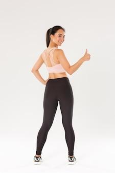 In voller länge von motivierten und zufrieden lächelnden asiatischen trainerin, mädchen athleticin sportswear drehen sich nach hinten, um daumen hoch zu zeigen, bereit für produktives fitnesstraining, weiße wand.