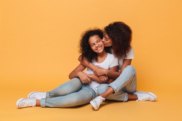 In voller länge von zwei glücklichen afrikanischen sitzenden und küssenden schwestern