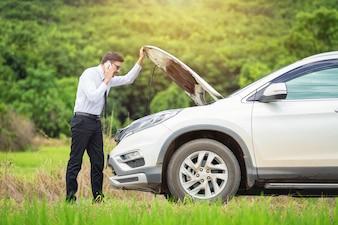 In voller Länge von besorgtem Geschäftsmann durch aufgegliedertes Auto an der Landschaft.