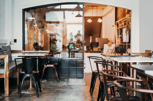 In warmen farben dekorierter kaffee im café lässt es warm aussehen zum ausruhen oder sitzen geeignet die ladenmöbel sind mit braunen eisenstühlen ausgestattet. die tischplatte besteht aus weißem marmor. weiche sitz- und tonregelung