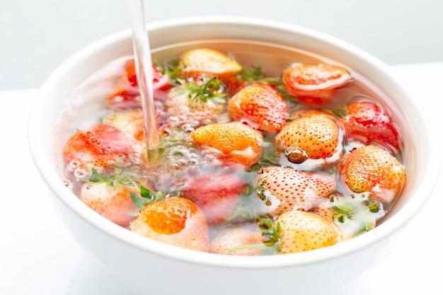 In wasser getränkte erdbeeren. waschen von frischem obst auf weiß.