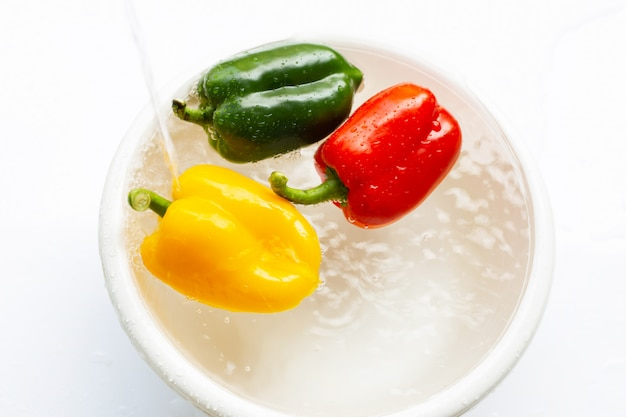 In wasser getränkter paprika. waschen des frischgemüses auf weiß