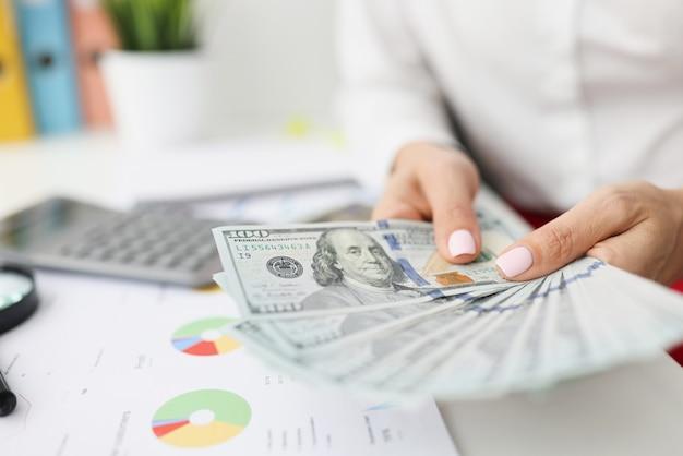 In weiblichen händen sind hundert-dollar-scheine auf dem tisch handels- und finanzzahlen in diagrammen