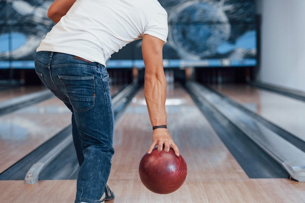 In weißem hemd und jeans. hintere partikelansicht des mannes in der freizeitkleidung, die bowling im club spielt