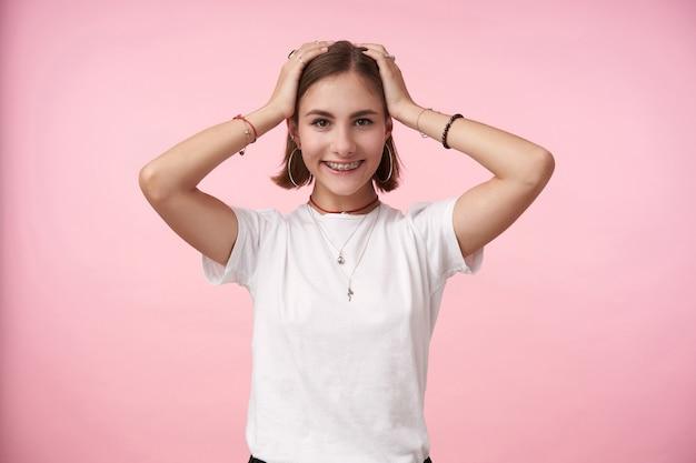 Inddoor-aufnahme einer jungen, charmanten, dunkelhaarigen frau, die ihre hände auf dem kopf hält, während sie mit einem breiten lächeln positiv nach vorne schaut und über einer rosa wand steht