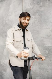 Inder, der einen elektroroller reitet. mann mit kaffee.