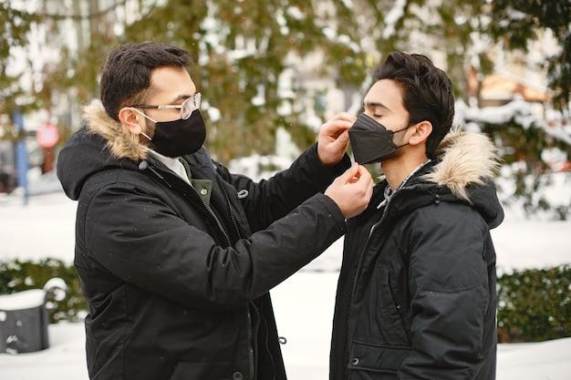 Inder in masken. männer auf der straße im winter. jungen tragen masken.