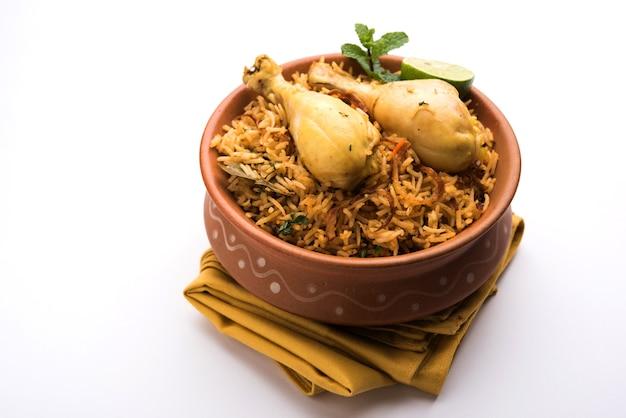 Indian chicken biryani serviert in einer terrakotta-schüssel mit joghurt auf weißem hintergrund. selektiver fokus