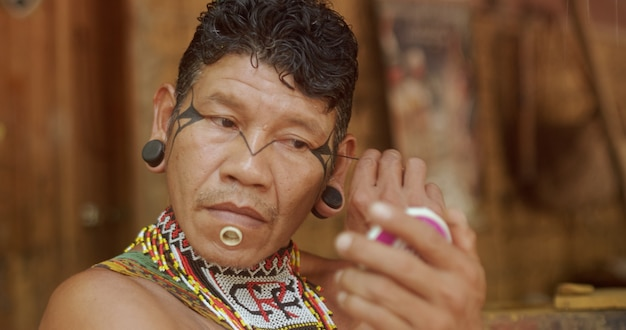 Indianer vom pataxo-stamm mit einem spiegel und schminken