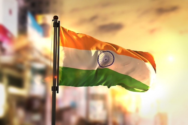 Indien flagge gegen stadt verschwommen hintergrund bei sonnenaufgang hintergrundbeleuchtung