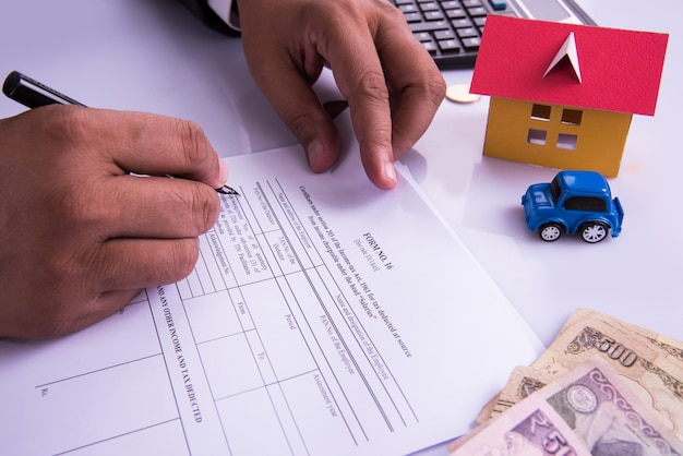 Indien und buchhaltungskonzept, das buchhalter zeigt, die an einkommensteuerformularen mit geldscheinen, taschenrechner und haus- und automodellen arbeiten