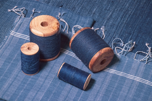 Indigofarbenes garn auf rollen- und indigofarbenem gewebtem stoffhintergrund