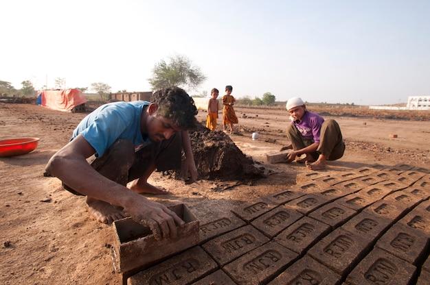 Indische arbeiter, die traditionelle ziegel von hand in der ziegelfabrik herstellen