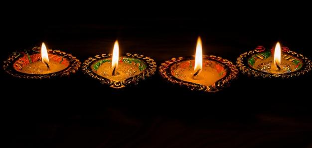 Indische art von vier brennenden bunten kerzen für diwali-feier auf schwarzem hintergrund. vertikale.