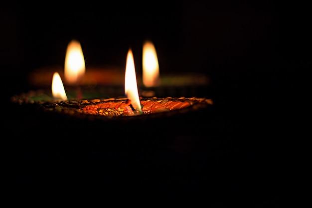 Indische art von vier brennenden bunten kerzen für diwali-feier auf schwarzem hintergrund.