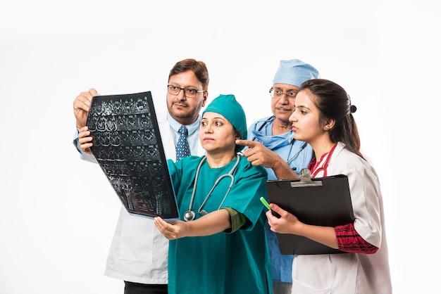 Indische asiatische ärzte, die ein röntgenbild oder ein mrt suchen, isoliert auf weißem hintergrund. selektiver fokus