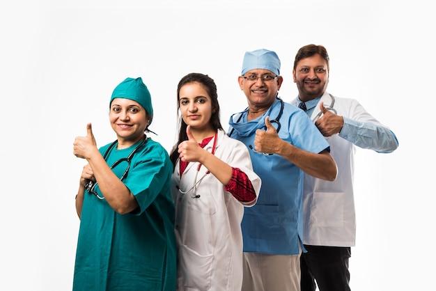 Indische asiatische ärzte gruppenfoto mit erfolg oder daumen hoch zeichen. stehend auf weißem hintergrund isoliert. selektiver fokus