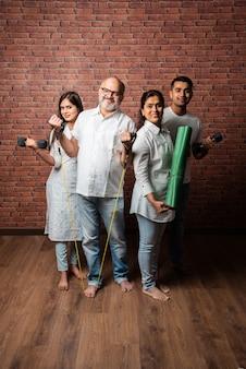 Indische asiatische familie, die zu hause trainiert. ältere eltern mit kleinen kindern, die yoga machen, gewicht heben, theraband im wohnzimmer verwenden. indoor-trainingskonzept