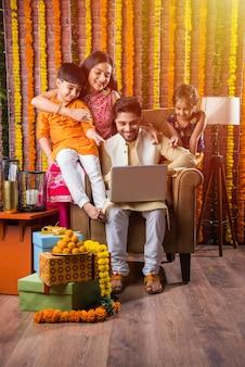 Indische asiatische junge familie, die online in der diwali festival night mit elektronischer karte und laptop einkaufen