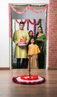 Indische asiatische smarte familie begrüßt lakshmi oder laxmi idol beim diwali festival mit pooja thali und süßigkeiten. an der eingangstür stehen