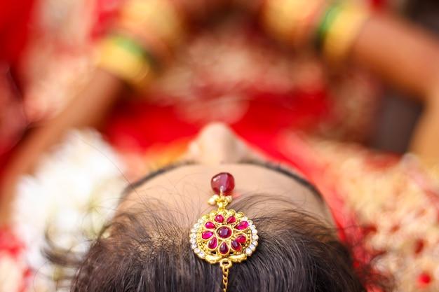 Indische braut, die hochzeitsfrisur und kopfschmuck zeigt