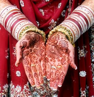 Indische braut, die mehndi-design und goldarmband und bunten armreif zeigt